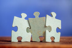 Three jigsaw puzzle pieces on a table Royalty Free Stock Photos