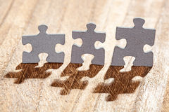 Three Jigsaw Puzzle Pieces on Table Lit by Back light Royalty Free Stock Photos