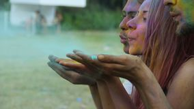 Three joyful friends blowing colorful paint in air and celebrating Holi festival. Stock footage stock video footage