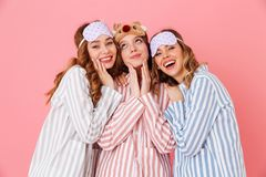 Three joyful girlfriends 20s wearing leisure clothings and sleep. Masks hugging and having fun at slumber party isolated over pink background Royalty Free Stock Photo
