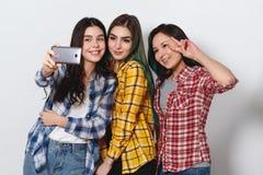 Three joyful girls girlfriends are doing selfie. smiling. light gray background royalty free stock photography