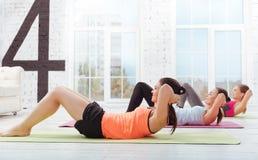 Three joyful women doing pushups in gym Stock Photos