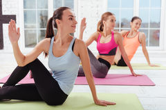 Three joyful women doing stretching exercise Stock Images