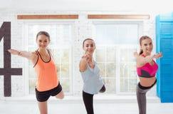 Three joyful women posing after training in fitness studio Royalty Free Stock Images