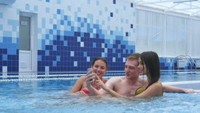Three joyful young friends taking selfies in the swimming pool stock video footage