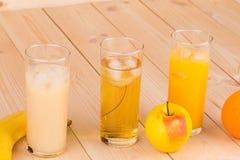 Three juices orange apple banana on wood. Royalty Free Stock Image