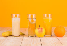 Three juices on orange background. Royalty Free Stock Photography