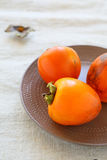 Three juicy ripe persimmon on a plate Stock Images