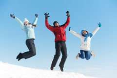 Three jumping young people in winter. Group of young people jumping on snow at winter outdoors Stock Photo