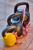 Three kettlebells on flagging Stock Images