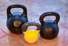 Three kettlebells on flagging Royalty Free Stock Photos