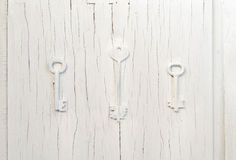 Three keys trendy decor on an old gray cracked door, vintage abstract design Stock Photo