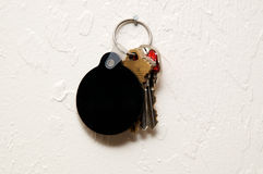 Three keys on wall with round blank black fob. A keyring with three keys and a round, blank, black key fob hanging on nail on wall Stock Photos