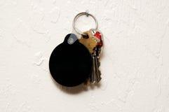 Three keys on wall with round blank black fob Stock Photos