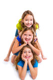 Three kid girls friends happy stacked in a row royalty free stock images