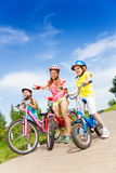 Three kid girls holding bicycles outdoors royalty free stock photo