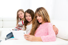 Three kid sister friends girls playing together with tablet pc. Three kid sister friends girls group playing together with tablet pc on white sofa Stock Photos