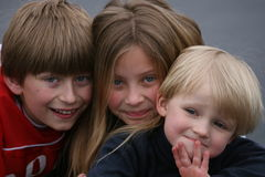 Three kids. Two boys and one girl showing faces and smile Stock Photos