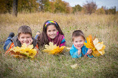 Three kids with autumn leaves Stock Photography