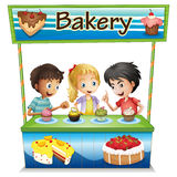 Three kids in a bakery stand with cupcakes Royalty Free Stock Photography