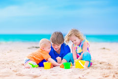 Three kids on a beach. Three kids, teen age boy, little toddler girl and a funny baby playing together digging in sand with colorful toys, spade and buckets Royalty Free Stock Photography