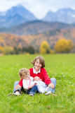 Three kids in beautiful snow covered mountains Stock Photos