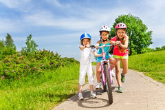 Three kids with a bicycle Stock Photography