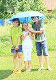 Three kids with blue umbrella. Little kids - barefoot girl and boys standing with a blue umbrella in sunny raining day Stock Photography