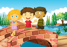 Three kids at the bridge Stock Photos