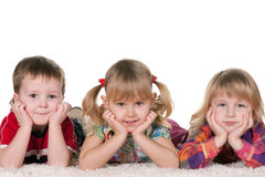 Three kids on the carpet Stock Image