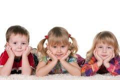 Three kids on the carpet stock image