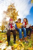 Three kids drawing and sitting on bench in autumn park. Group of three smiling happy kids friends, boys and girls sitting on the bench in the park under the Royalty Free Stock Photography