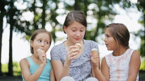 Three kids eat ice cream in waffle cone