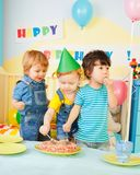 Three kids eating cake on the birthday party Stock Image