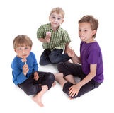 Three kids eating ice lolly Stock Image