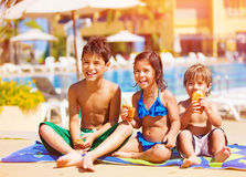 Three kids eating near pool. Three kids sitting down and eating croissant near pool, picnic outdoors, beach resort, summer vacation, happy childhood concept Stock Photography