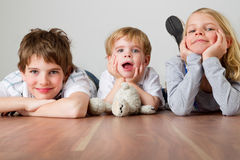 Three kids on the floor. Three kids are lying on their bellies on the floor royalty free stock images