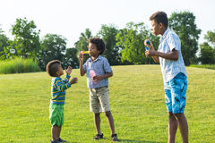 Three kids on glade with soap bubble. Royalty Free Stock Images