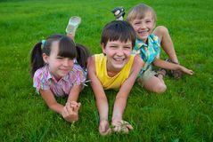 Three kids on grass Royalty Free Stock Image