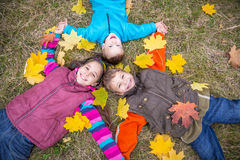 Three kids on grass with yellow leaves. Three happy kids lying together on withered grass with fallen yellow leaves, outdoors royalty free stock photo