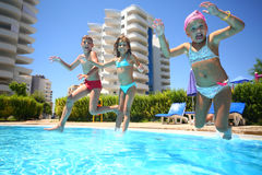 Three kids having fun jumping into the water the swimming pool. Shot through the underwater package stock images