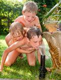 Three kids having fun palying with lawn sprinkler in a summer garden royalty free stock photos