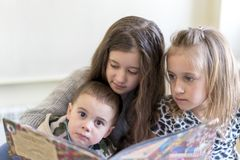 Three kids having fun reading a book. Two sisters and a brother. Light background. European appearance Royalty Free Stock Photography