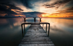 Three kids having fun on a wooden jetty during sun set down Royalty Free Stock Image