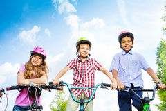 Three kids in helmets hold bike handle-bars Royalty Free Stock Photos
