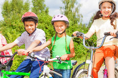 Three kids in helmets sitting on the bikes Royalty Free Stock Photos