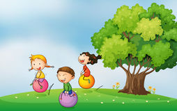 Three kids at hilltop playing with bouncing balls Stock Photo