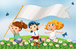 Three kids at the hilltop running with an empty banner Royalty Free Stock Image