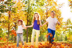 Three kids hold hands playing in the forest Stock Photography