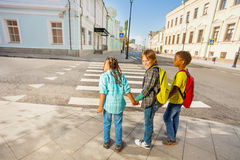 Three kids holding hands stand on street Stock Image